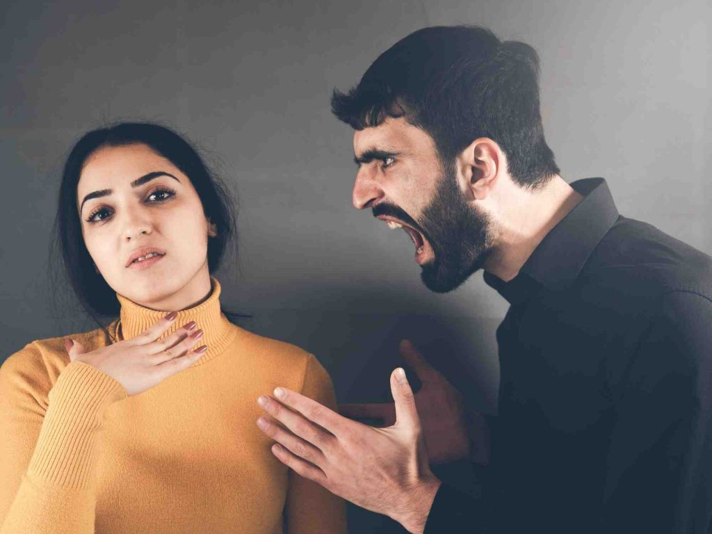 Angry man shouting at woman in a yellow jumper.
