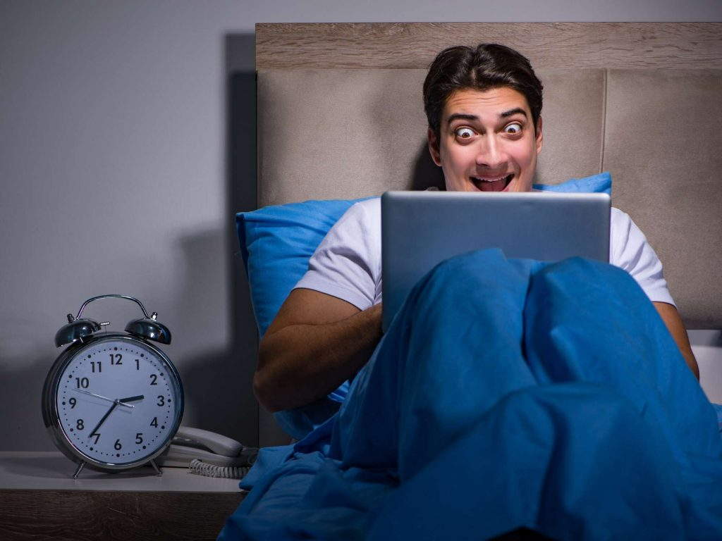 Happy man in bed on laptop.