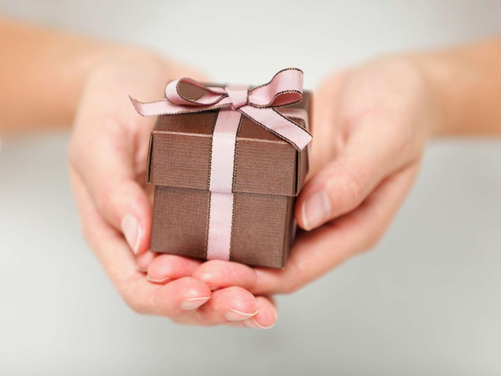 Woman holding small gift with ribbon.