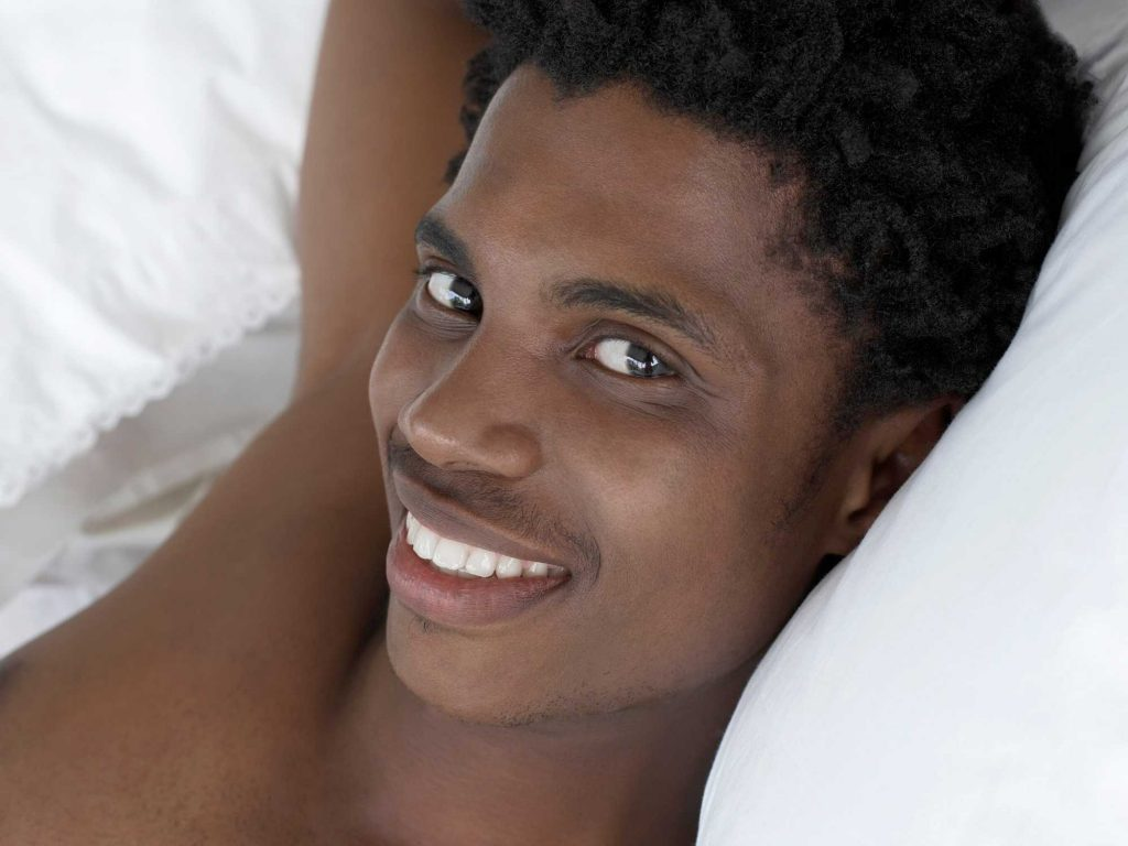 Smiling man in bed.