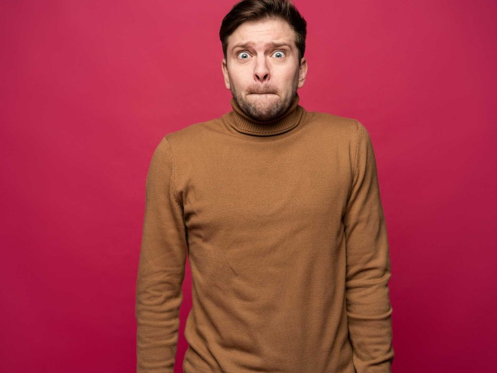 Nervous man in brown jumper against pink wall.
