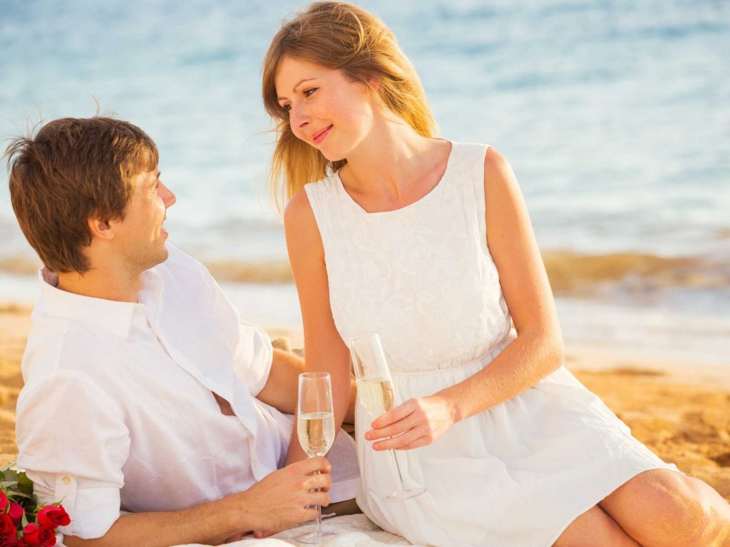 Couple drinking champagne on the beach.