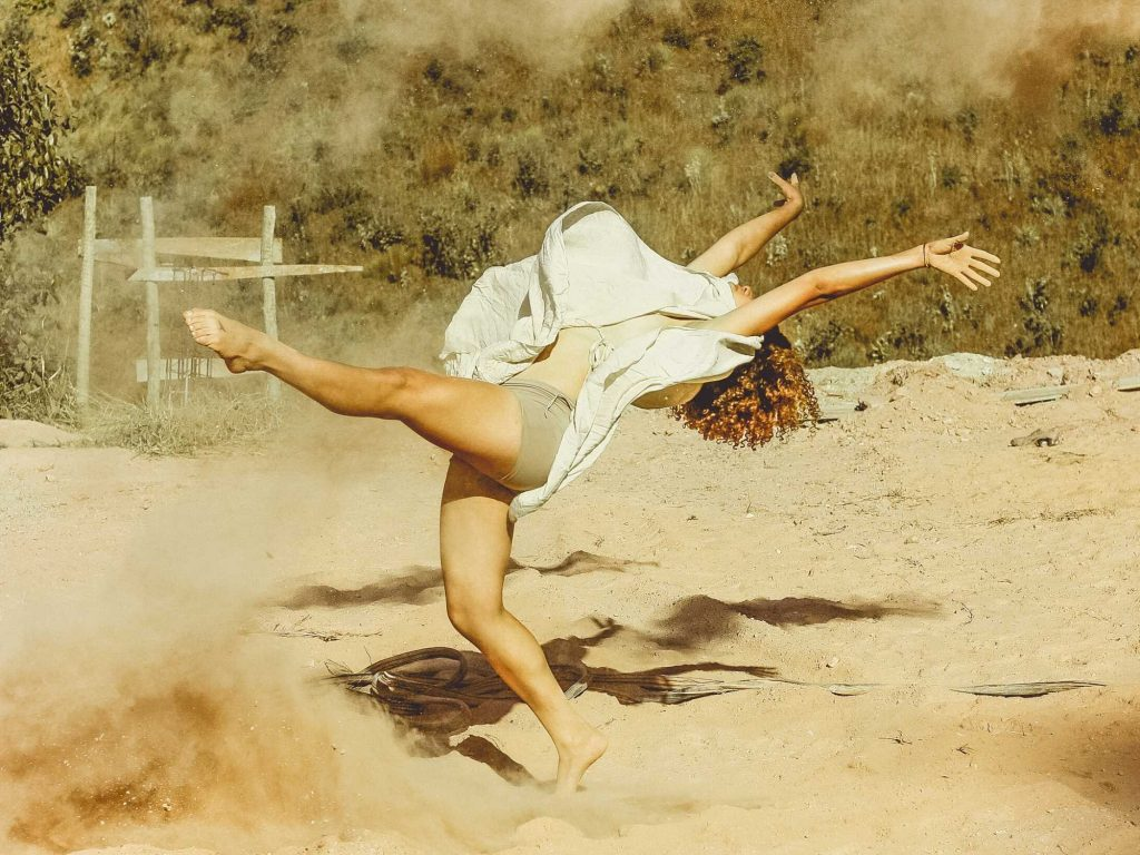Woman dancing in the sand.