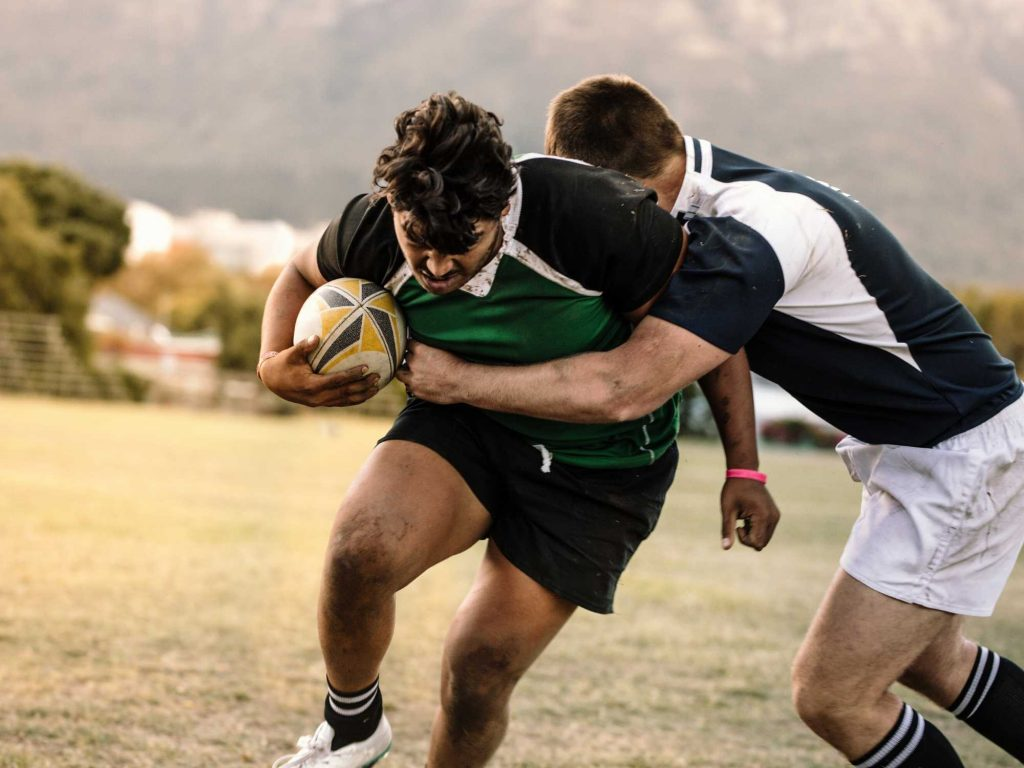 Man rugby tackling another man.