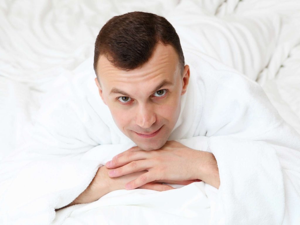 Man in white robe on white bedsheets.