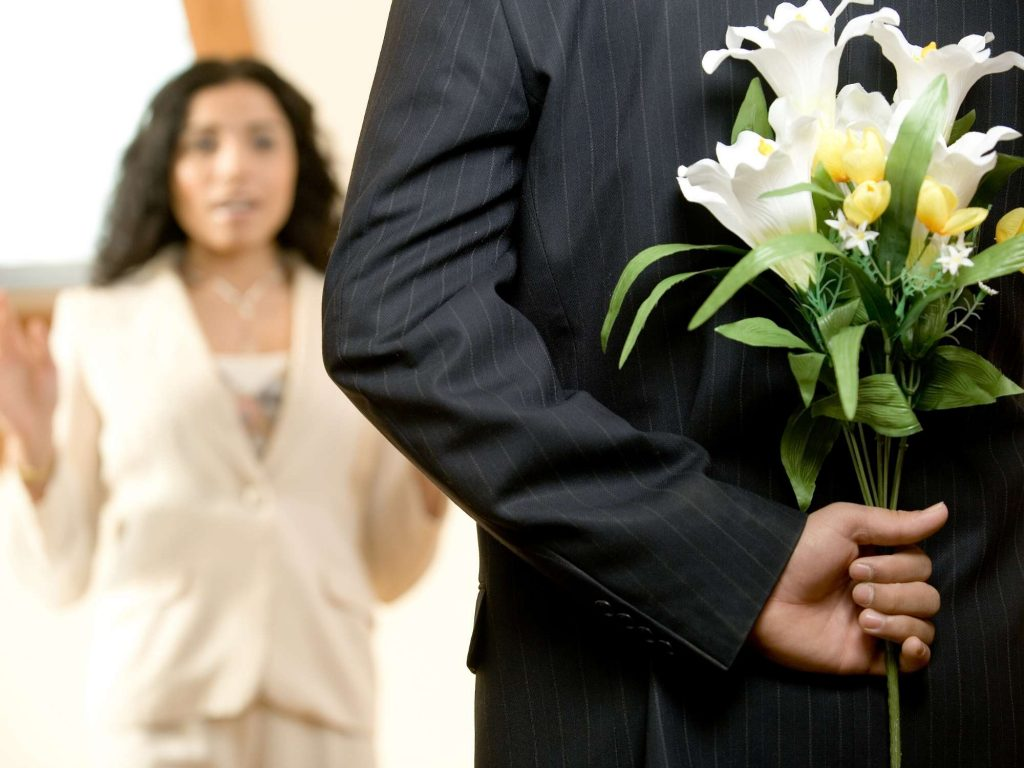 Man surprising woman with flowers behind his back.