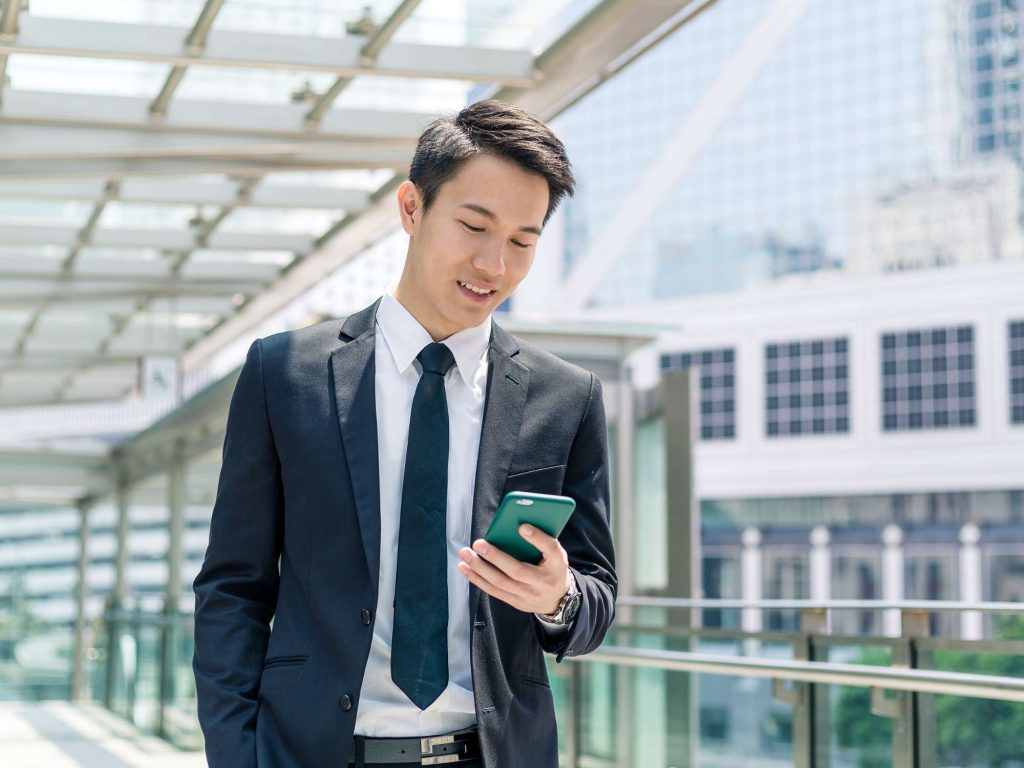 Man in suit looking at mobile phone.